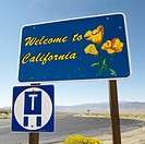 Welcome to California sign with strip of highway and clear blue sky in background