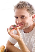 Man eating sandwich with salami (thumbnail)