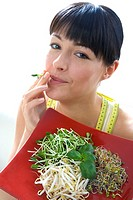 toung woman with various sprouts on plate