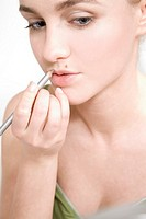 young woman putting on lipliner
