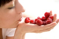 close_up of a woman with raspberries on hand