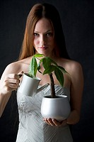 woman watering potted flower
