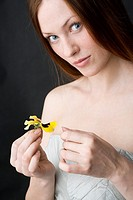 young woman with pansy in hand