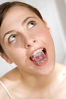 young woman with ice cube in mouth
