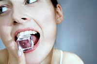 Young woman with ice cube in mouth (thumbnail)