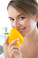 Young woman smelling yellow paprika (thumbnail)