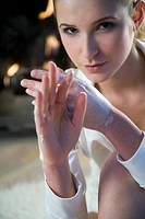 Woman creaming hands (thumbnail)