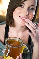 Young woman putting honey into lips (thumbnail)