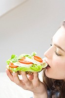 Young woman eating mozarella and tomatoe sandwich