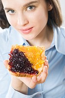 Young woman eating toast with jam