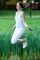 Young woman jumping rope in park