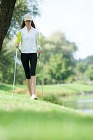 Young woman nordic walking in park