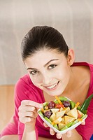 Young woman eating fruit salad (thumbnail)