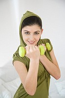 Young woman training with dumbbells (thumbnail)