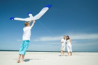 Family playing with kite on beach (thumbnail)
