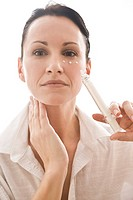 Woman applying eye cream (thumbnail)