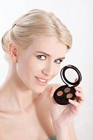 woman holding eye shadows