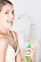 young woman applying body spray