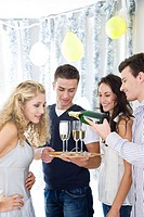 Friends drinking champagne at party (thumbnail)