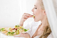 Woman eating fruit salad (thumbnail)