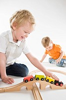 toddler boys playing with toy train set