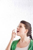 young woman using mouth freshener