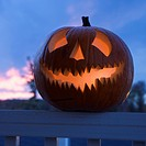 Carved Halloween pumpkin perched on porch railing