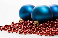 Still life of large blue Christmas ornaments and strings of red beads (thumbnail)