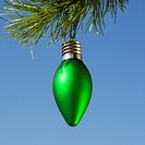 Green ornament hanging on Christmas tree branch against blue background