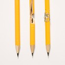 Whole pencil, broken pencil and stapled together pencil lined up against white background.