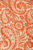 Close_up of orange textural vintage fabric with paisley and metalic thread stitching