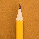 Close up of sharp pencil tip on tan background