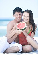 couple eating watermelon on beach