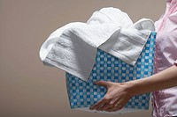 Young woman carrying laundry basket midsection