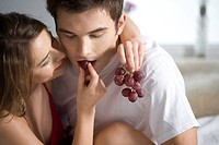 couple eating grapes in bed