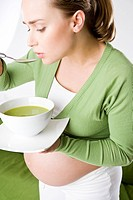 pregnant woman eating soup