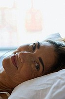 Close_up of a mature woman lying on the bed and smiling