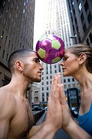 Side profile of a young woman and a young man with a soccer ball between their heads