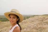 Hispanic girl in straw hat in remote field