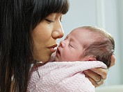 Mixed race mother cuddling newborn baby