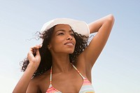 African woman in bikini holding hat in wind