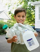Boy carrying empty recyclable bottles