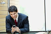 Mixed race businessman looking at cell phone