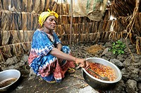 Woman cooking in her tent at the refugee camp  Mugunga 1, west of Goma, North Kivu, Democratic Republic of Congo, Africa