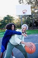 African woman playing basketball with granddaughter