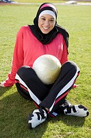 Muslim teenager sitting on ground with soccer ball