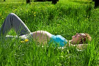 Pregnant woman relaxing in grass field