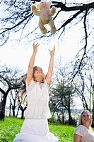 Girl tossing teddy bear in park