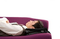 Businessman using briefcase as pillow, asleep on sofa, close-up, cut out (thumbnail)