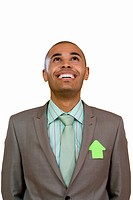 Businessman wearing arrow shaped post it on jacket, looking up, smiling, cut out (thumbnail)